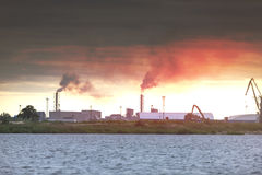 Air pollution by smoke coming out of two factory chimneys. Industrial zone in the city Stock Images