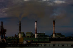 Air Pollution. 3 smoke stacks from a seaside industrial complex in S.E. Asia heavily polluting the air Royalty Free Stock Image