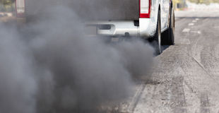 Air pollution from vehicle exhaust pipe on road Royalty Free Stock Photo