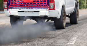 Air pollution from vehicle exhaust pipe on road Stock Photos