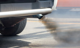 Air pollution from vehicle exhaust pipe on road Stock Images