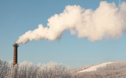 Air polution. Smoke from a pipe on the background of sky Stock Images