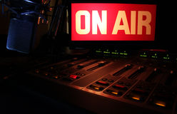 On-Air Radio Panel. On Air sign glowing, reflecting light on a radio studio broadcast panel