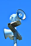 Air raid siren against blue sky Stock Image