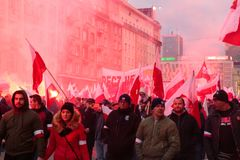 Independence Day March in Warsaw Poland Marred by Violence and Controversy. The air is red from the smoke released from nearby flares as protesters wave polish Stock Images