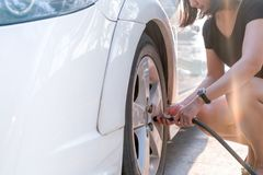 Air remplissant de conducteur dans un pneu de voiture, inflation de pneu photographie stock