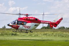 Air rescue ambulance helicopter in flight. AHLEN GERMANY - JUN 5 2016: DRF Luftrettung German Air Rescue BK-117 helicopter landing at Ahlen-Nord heliport stock image