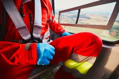 Air rescue service. Alarm for the air rescue service. Doctor is preparing in the helicopter emergency medical service. - selective focus on the glove stock image