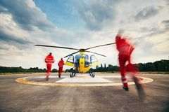 Air rescue service. Alarm for the air rescue service. Team of rescuers (paramedic, doctor and pilot) running to the helicopter on the heliport stock images