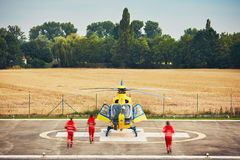 Air rescue service. Alarm for the air rescue service. Team of rescuers (paramedic, doctor and pilot) running to the helicopter on the heliport royalty free stock image