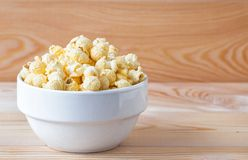 Air salty popcorn. A bowl of popcorn on a wooden table. royalty free stock photos