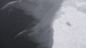 Air shot tilt up of frozen river with ice layers. Air shot tilt up of frozen river. Dark water of river in winter time shot from above. Snow falling on frozen stock footage