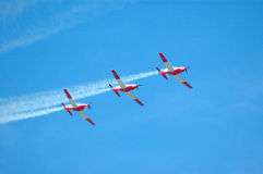 Air show. Three airplanes in red and white flying in a flight formation in the air at an air show Stock Photos