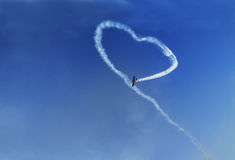 Air show. White Smoke Heart On Blue Sky Royalty Free Stock Image