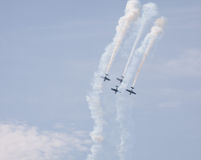 Air show. Old planes flying and diving in formation with smoke streams at an air show Stock Images