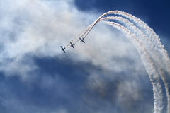 Air Show. The view of the white plane trails on the blue sky background Royalty Free Stock Photo
