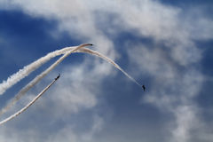 Air Show. The view of the white plane trails on the blue sky background Stock Photos