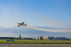 Air show. Aerobatic plane flying close to the ground with smoke trail at the Bucharest Air Show on June 22, 2014 in Bucharest, Romania Royalty Free Stock Images