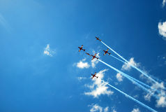 Air show with red jets across bright blue skies Stock Photography