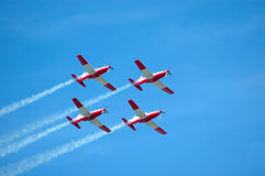 Air show team. A team of four airplanes in red and white flying together high up in the sky on an air show Royalty Free Stock Photos