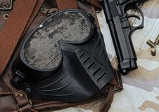 Air-soft gun and mask. Air-soft mask lying over a Leather handbag, Face protection from BB Gun Shooting game stock image