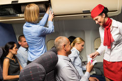 Air stewardess check ticket airplane cabin smiling Royalty Free Stock Photo