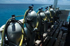 Air tanks. Several scuba cylinders on boat, ocean in background Royalty Free Stock Photography