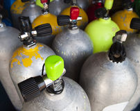 Air Tanks Filled For A Dive. A set of air tanks that have been prepared for a diving expedition. The focal point is on the green cap of the closest tank and the stock image