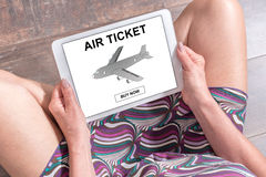 Air ticket booking concept on a tablet. Woman sitting on the floor with a tablet showing air ticket booking concept Royalty Free Stock Image