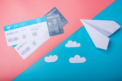 Air tickets and paper plane on pastel background, topview. Concept of air travel and holidays. Air tickets and paper plane on pastel background, topview. The royalty free stock images