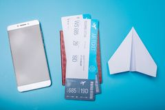 Air tickets with passport and paper plane on blue background, topview. The concept of air travel and holidays. Air tickets with passport and paper plane on blue Stock Images