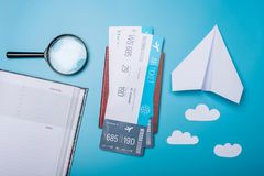 Air tickets with passport and paper plane on blue background, topview. The concept of air travel and holidays. Air tickets with passport and paper plane on blue stock image
