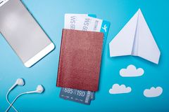 Air tickets with passport and paper plane on blue background, topview. The concept of air travel and holidays. Air tickets with passport and paper plane on blue Royalty Free Stock Photography