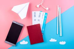 Air tickets with passport and paper plane on pastel background, topview. The concept of air travel and holidays. Air tickets with passport and paper plane on Royalty Free Stock Image