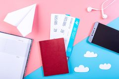 Air tickets with passport and paper plane on pastel background, topview. The concept of air travel and holidays. Air tickets with passport and paper plane on Stock Photo