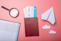Air tickets with passport and paper plane on pink background, topview. The concept of air travel and holidays. Air tickets with passport and paper plane on pink Royalty Free Stock Photo