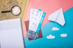 Air tickets with passport and paper plane on world map background, topview. The concept of air travel and holidays. Air tickets with passport and paper plane on Royalty Free Stock Image