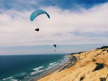 Air time. An enjoyable beach day watching hang gliders Royalty Free Stock Images