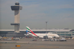 Air Traffic Control Tower and Emirates Airlines Airbus A380 at John F Kennedy International Airport. NEW YORK- JUNE 9, 2017: Air Traffic Control Tower and Royalty Free Stock Image