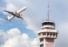 Air traffic control tower in international airport with passenger airplane jet taking off. On blue sky background Stock Image