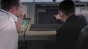 ASTANA, KAZAKHSTAN - JANUARY 7, 2018: air traffic controllers discuss the plan of movement of aircraft on a computer
