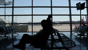 Air transportation concept. Silhouettes of passengers waiting for their flight against large terminal window at the airport stock video footage