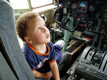 Air Travel. This young boy is amazed by all the controls inside a military aircraft Stock Image