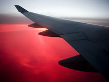 Air travel. Concept, plane wing above sunset or sunrise clouds in red color stock images
