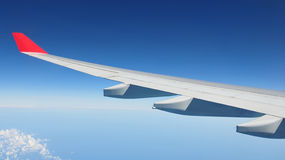 Air Travel. Theme of an Airplane Wing against a Vivid Blue Sky and Ocean with Plenty of Copy Space Stock Photos