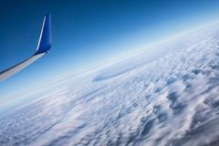 Air travel above the clouds, tilted view. View from an airplane on a thick cover of clouds above the ocean, with an airplane wing in the corner, tilted view Royalty Free Stock Photos