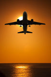 Air travel airplane. Silhouette fyling against the sun and water - summer vacation holiday concept Royalty Free Stock Image