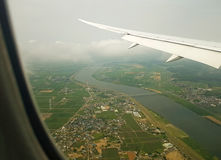 Air travel-airplane window view of landscape. View of below land and water from an airplane window while it is coming to land at the airport. Also the span of Stock Photo