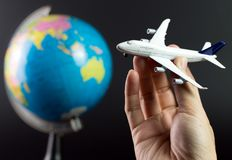 Air travel around the world. Hand holding airplane flying around the globe over black background Stock Photos