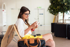 Air travel concept. Young woman with hand luggage and modern technology. Royalty Free Stock Images